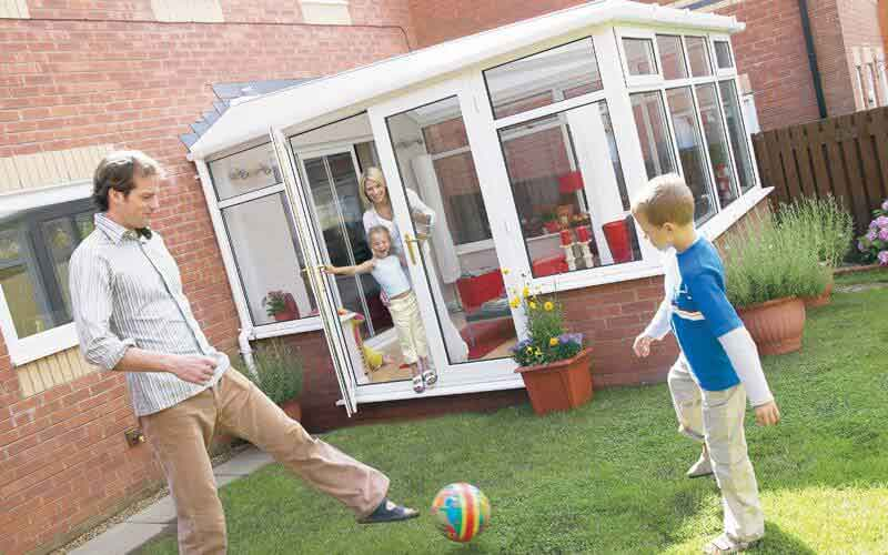 Lean-to conservatory with family outside